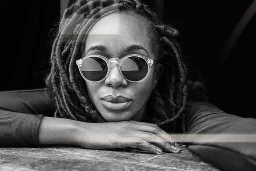 Portrait of woman with dreadlocks wearing sunglasses in front of black background
