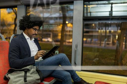 Spain, Barcelona, businessman in a tram at night using tablet