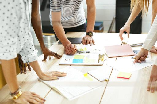 Close-up of colleagues working together at desk in office discussing papers