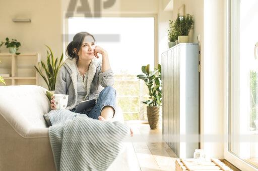 Smiling woman with a mug and tablet sitting on the couch at home