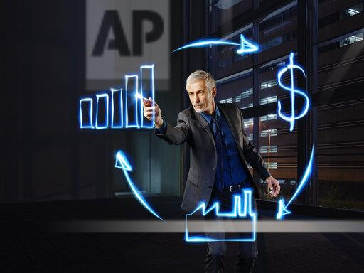 Businessman painting economic circulation with light