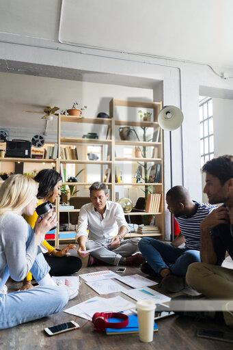 Business team sitting on floor discussing documents in loft office