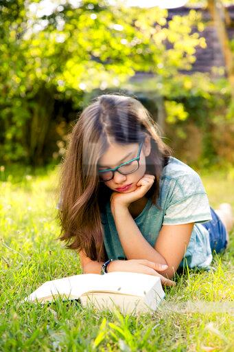 Girl lying on a meadow in garden reading book