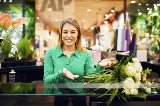 Portrait of smiling florist presenting bunch of flowers in flower shop