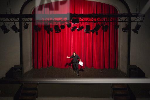 Rehearsing actor with script standing on theatre stage in front of red curtain