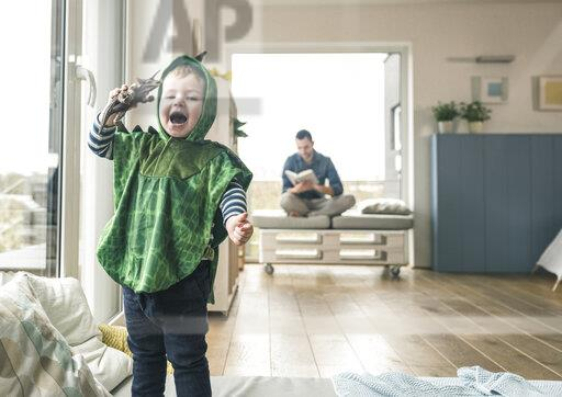 Happy boy in a costume playing with toy figure at home