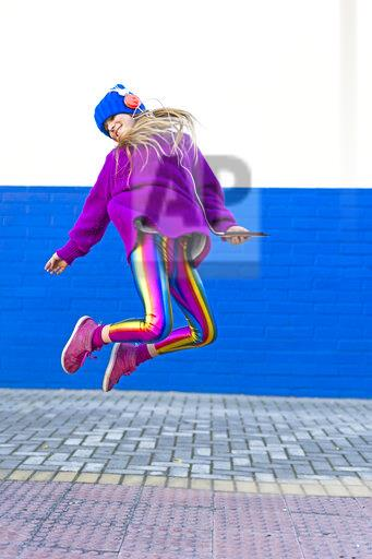 Happy girl with headphones and smartphone jumping in the air