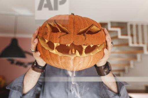 Man holding Jack O'Lantern in front of his face, smoke