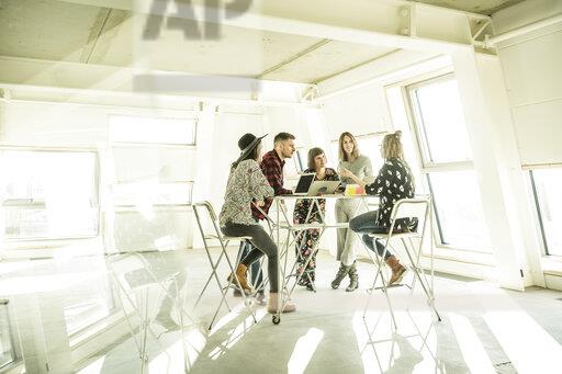 Group of creative professionals having a meeting in a bright office, discussing new solutions