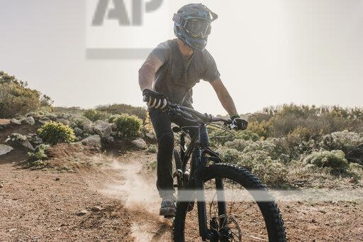 Spain, Lanzarote, mountainbiker on a trip in desertic landscape