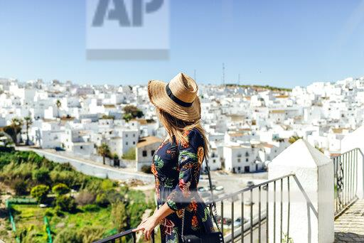 Spain, Cadiz, Vejer de la Frontera, fashionable woman standing on roof terrace looking at view