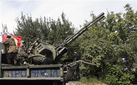 A Pro-Russian rebels truck with an anti-aircraft weapon is driven in a parade in the town of Luhansk, eastern Ukraine, Sunday, Sept. 14, 2014. Some semblance of normality is returning to parts of eastern Ukraine after a cease-fire agreement sealed between Ukrainian government forces and separatist rebels earlier this month, although exchanges of rocket fire remain a constant in some areas. (AP Photo/Darko Vojinovic)