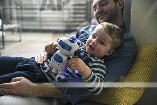 Father and son playing with a toy robot at home