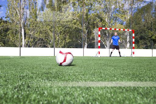 Football on grass with goalkeeper in the background