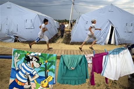 Boys play at a refugee camp set up by the Russian Emergencies Ministry for people displaced by fighting in Ukraine, about 10 kilometers (6 miles) from the Russia-Ukrainian border, near Donetsk, Rostov-on-Don region, Russia, Monday, Aug. 18, 2014. Fighting across eastern Ukraine has forced nearly 344,000 people to flee their homes, according to U.N. figures released Friday. The U.N. says about 155,800 have left for other places inside Ukraine while 188,000 more have crossed into Russia. (AP Photo/Pavel Golovkin)