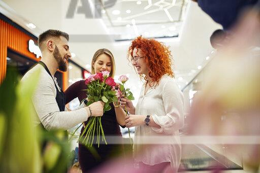 Florist advising customers in flower shop