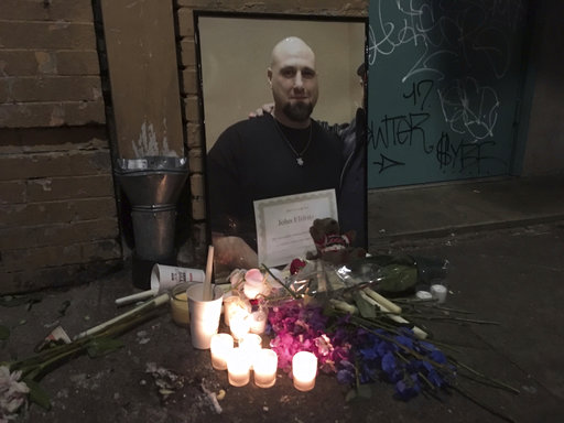 In this Sunday, April 8, 2018 photo, candles burn in front of a makeshift  memorial for John Andrew Elifritz outside City Team Ministries in Portland,  Ore.