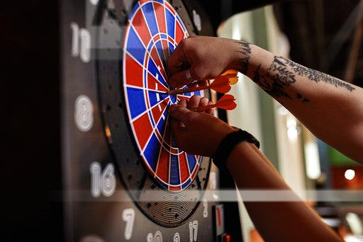 Close-up of tattooed man taking out darts from electronic dartboard