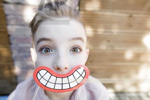 Blond boy with grinning mouth mask