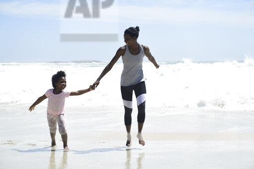 Happy mother and daughter having fun on the beach