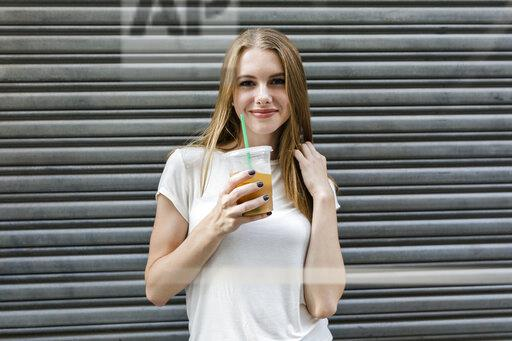 Young woman in the city drinking take-out coffee