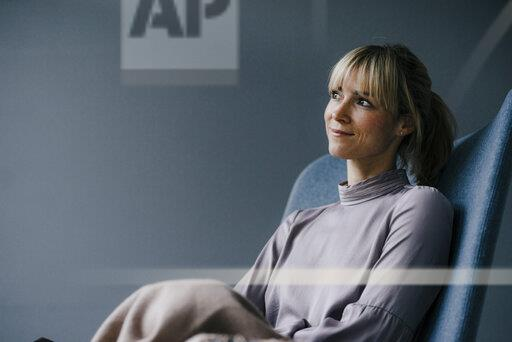 Blond woman sitting in armschair, daydreaming