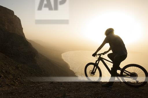 Spain, Lanzarote, mountainbiker on a trip at the coast at sunset enjoying the view