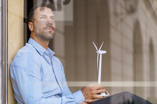 Businessman with wind turbine model behind windowpane thinking