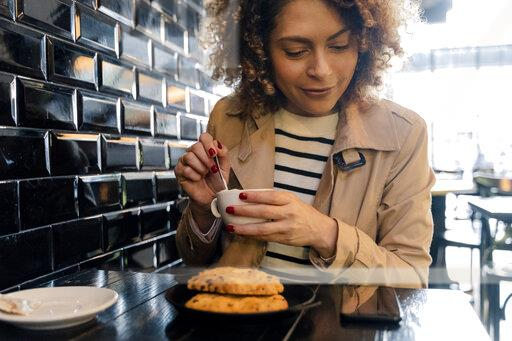 Smiling woman looking at cell phone in a cafe