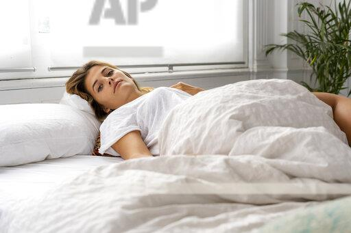 Portrait of beautiful young woman lying in bed