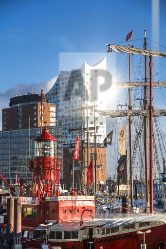 Germany, Hamburg, Sailing ship moored in harbor withElbe Philharmonic Hall in background