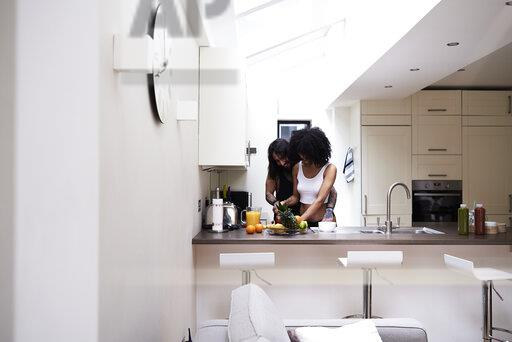 Affectionate young couple preparing healthy meal in kitchen