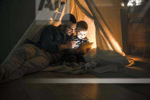 Father and son sharing a tablet in a dark tent at home