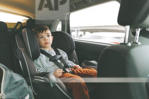 Little boy sitting in car on child's seat with fastened seat belt