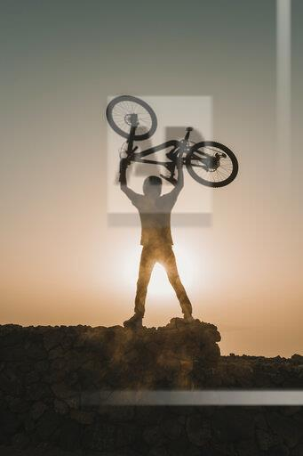 Spain, Lanzarote, mountainbiker on a trip at sunset lifting up his bike