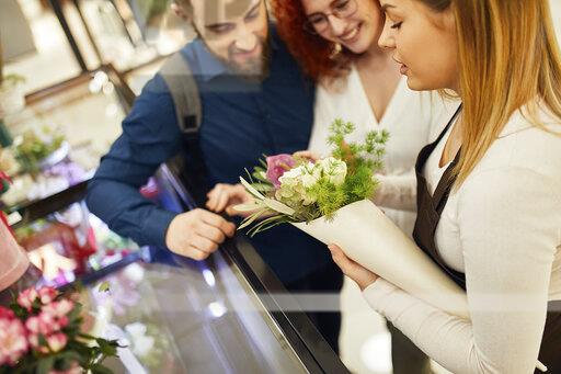 Florist wrapping flowers for couple in flower shop