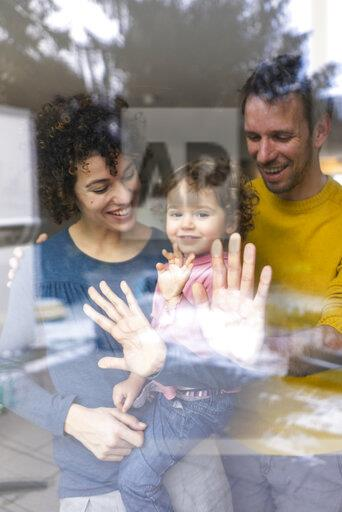 Family looking out of window, mother carrying daughter, touching glass pane