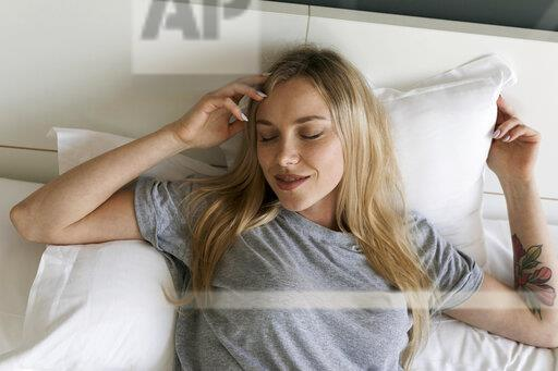 Smiling blond young woman lying in bed