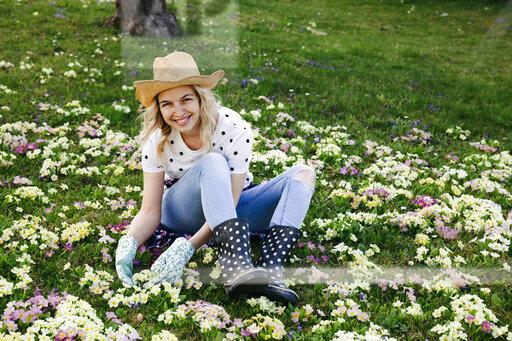 Young woman is sitting in flower meadow