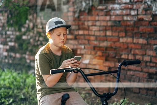 Boy with bmx bike using cell phone