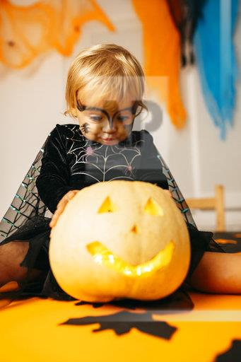 Portrait of little girl with painted face and fancy dress sitting on table with Jack O'Lantern pouting mouth