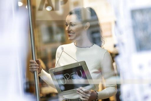 Mature woman standing in shop , smiling, with open sign hanging in window