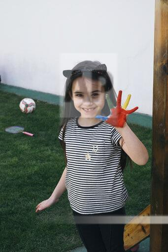 Girl smiling and showing her painted palm
