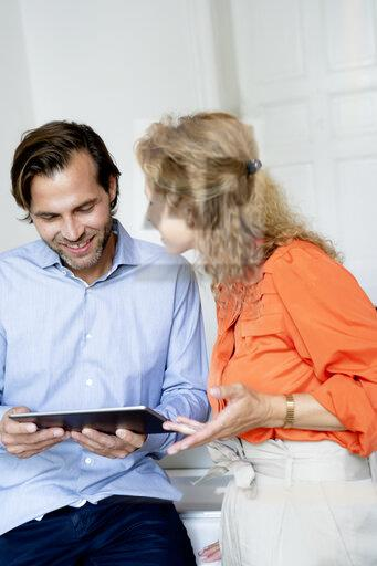 Happy couple working from home, discussing over digital tablet