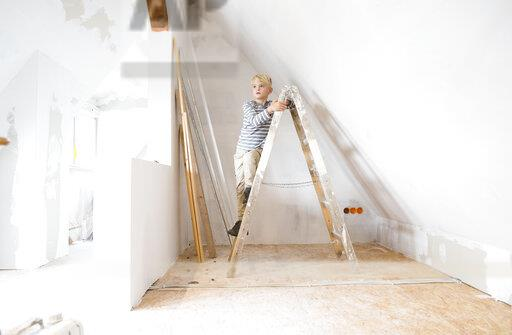 Boy standing on ladder in attic to be renovated