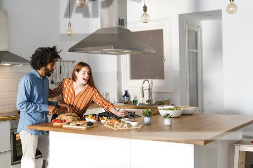 Couple standing in kitchen, preparing dinner party