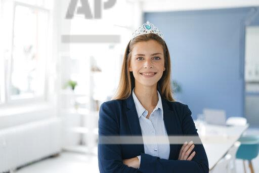 Ambitious young woman wearing crown as an award for her achievements