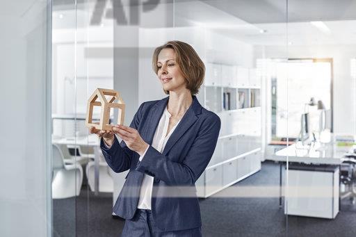 Smiling businesswoman looking at architectural model in office
