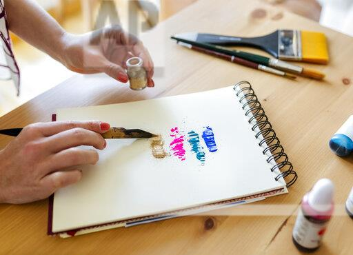 Woman's hand applying colour pigments on colouring book