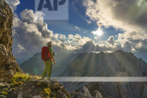 Italy, Veneto, Dolomites, Alta Via Bepi Zac, mountaineer standing on Costabella mountain at sunset